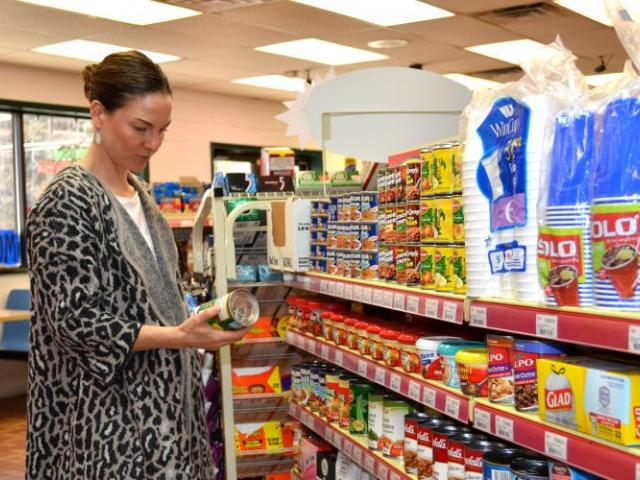 Alison Gustafson, UK associate professor, looks at nutrition labels of items in an Inez convenience store