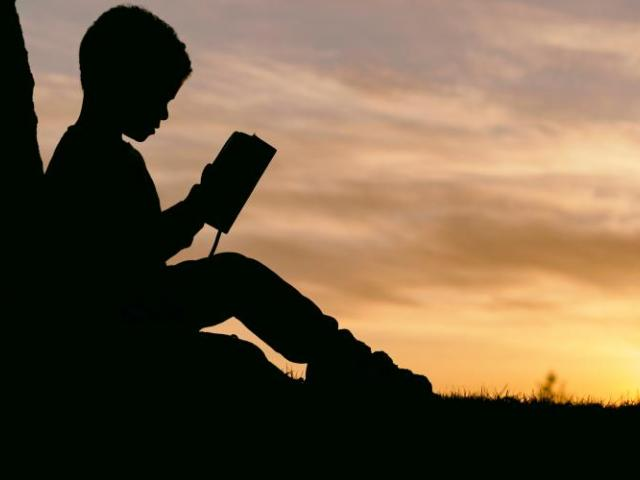 Silhouette of child with a book