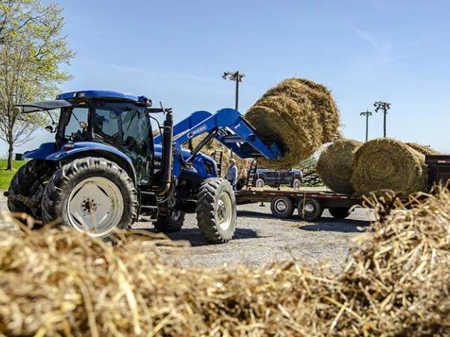 tractor moves donated hay